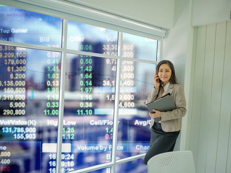Nowożytny biznesowych kobiet use telefon komórkowy opowiadał rynek papierów wartościowych zdjęcie royalty free