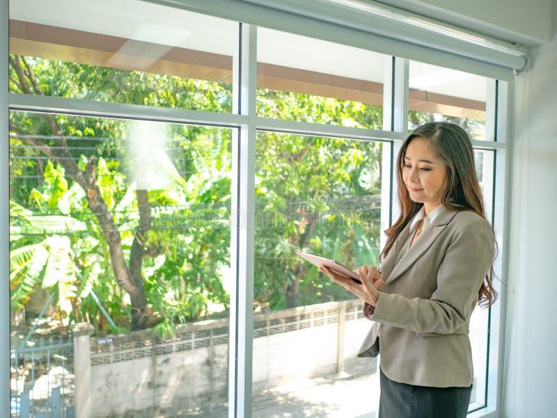 Nowożytny biznesowych kobiet use telefon komórkowy opowiadał rynek papierów wartościowych obraz stock