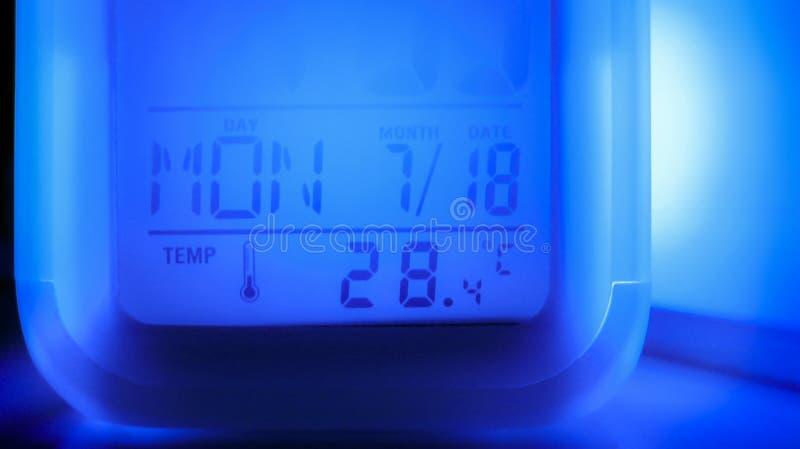 Nowożytny cyfrowy zegar z błękita lekkim pokazuje czasem, datą i temperaturą, zdjęcie stock