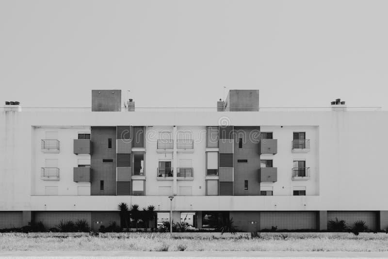 Nowożytny dom z balkonami i okno w czarny i biały z roślinami i drzewami w przodzie obraz stock