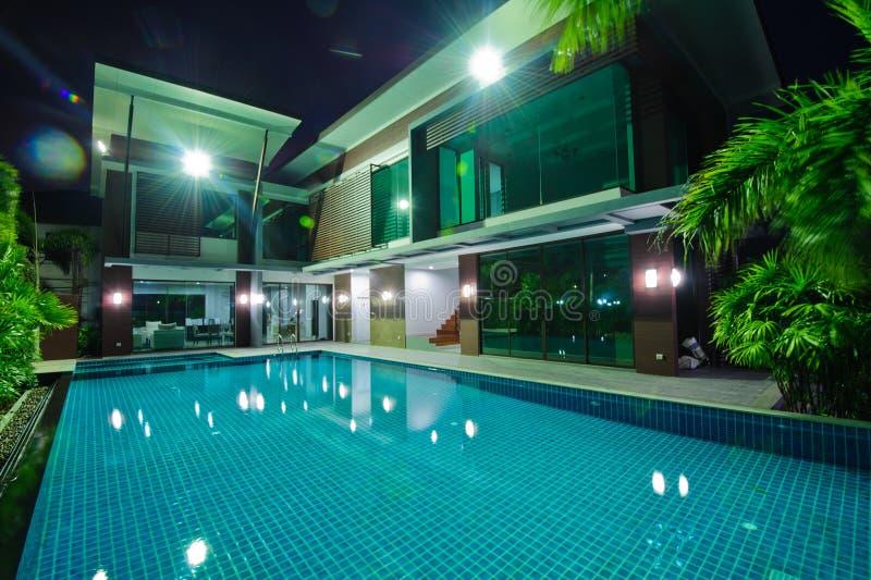 Nowożytny dom z pływackim basenem przy nocą zdjęcie royalty free