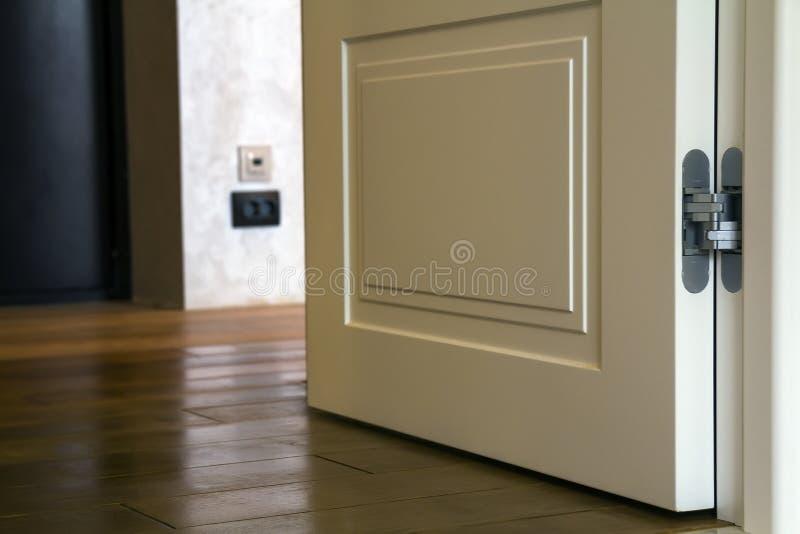 Nowożytny domowy wewnętrzny szczegół z drewnianą parkietową podłoga i białym drzwi Mieszkanie po odświeżania zakończenia obraz stock