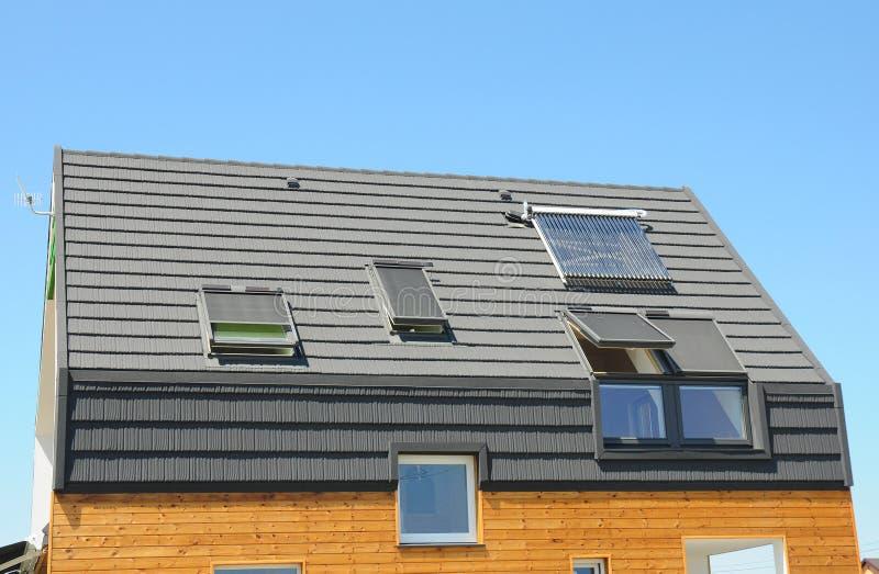 Nowożytny domu dach z Słonecznym Wodnym nagrzewaczem, panel słoneczny i Skylights, Piękny Nowy rówieśnika dom z panel słoneczny zdjęcie stock