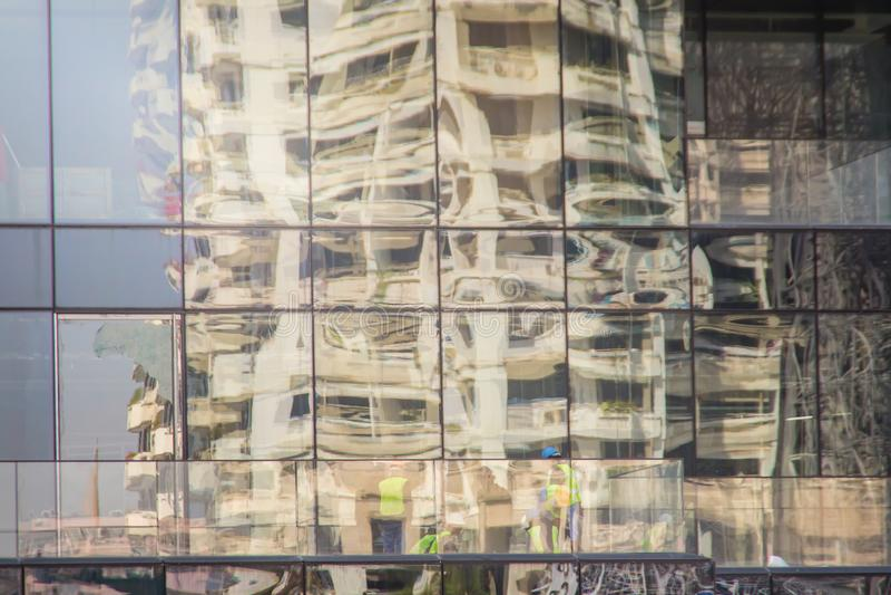 Nowożytny drapacza chmur budynek z szkłem odbija pracowników w budowie Abstrakcjonistyczny odbicie budynek biurowy z obrazy stock