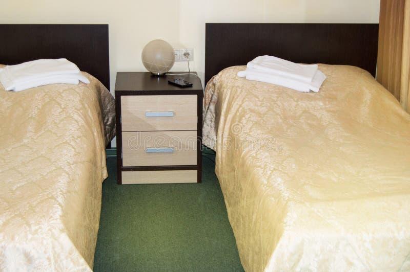 Nowożytny dwoisty pokój z dwa pojedynczymi łóżkami, wezgłowie stołem, ręcznikami i stołową lampą, wygodny niedrogi pokój dla podr zdjęcia stock