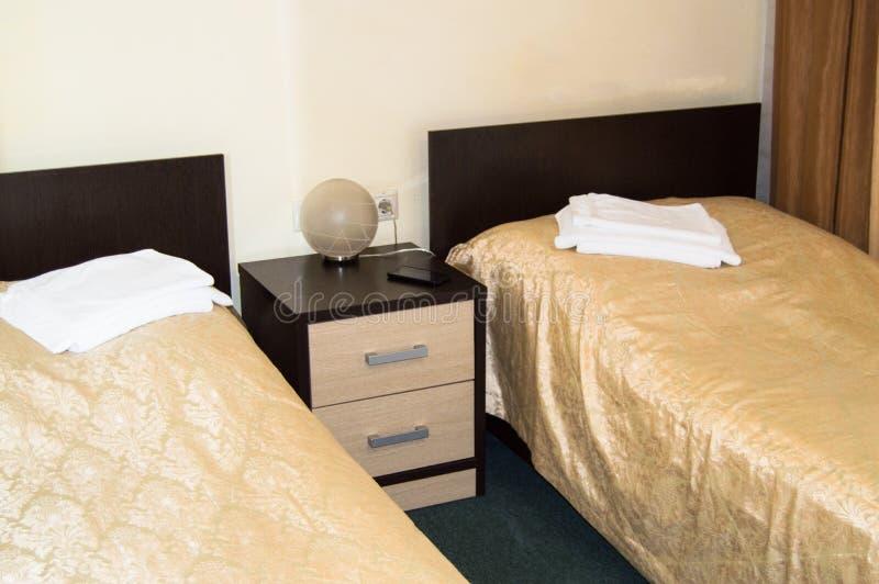 Nowożytny dwoisty pokój z dwa pojedynczymi łóżkami, wezgłowie stołem, ręcznikami i stołową lampą, wygodny niedrogi pokój dla podr obraz royalty free