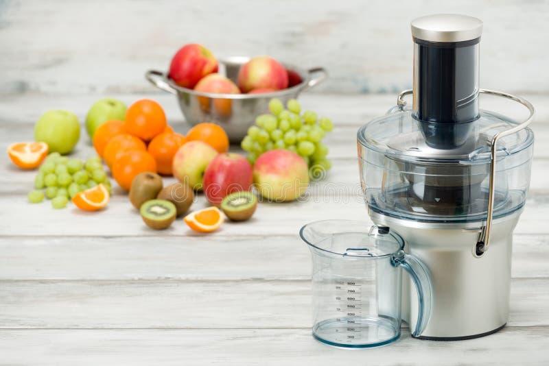 Nowożytny elektryczny juicer i różnorodna owoc na kuchennym kontuarze, zdrowy styl życia fotografia stock