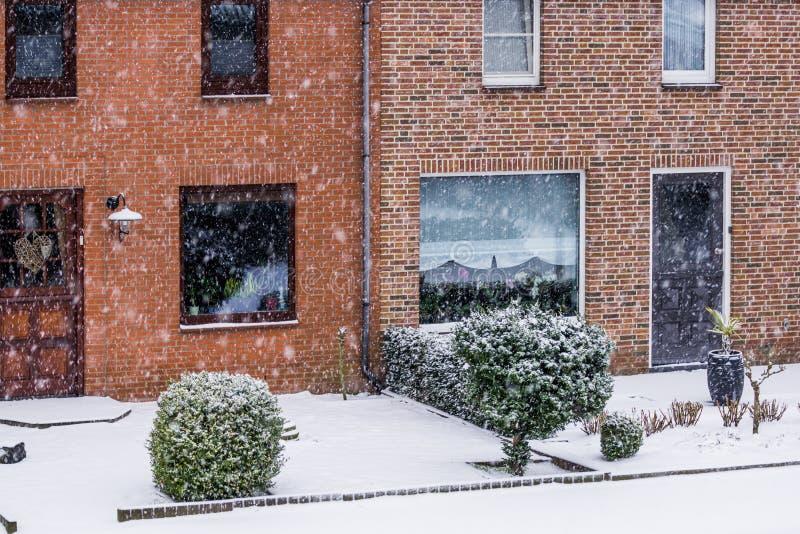 Nowożytny holender tarasował domy z ogródem podczas zimnego zima dnia, śnieżna pogoda w małej wiosce holandie zdjęcia royalty free