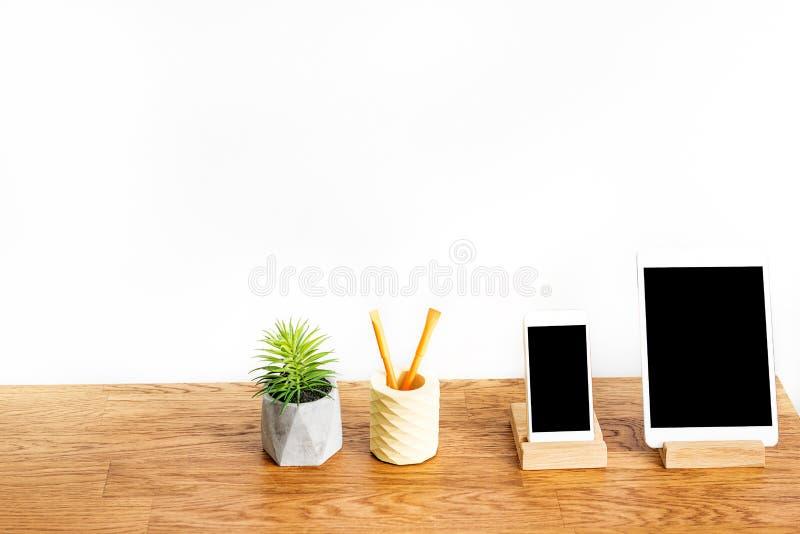 Nowożytny komputer z telefonem komórkowym i domowa roślina na stole ukazujemy się obraz stock