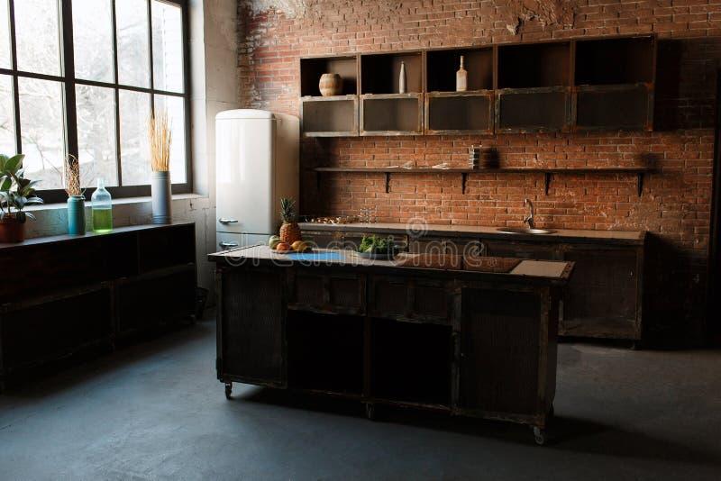 Nowożytny kuchenny wnętrze z czerwonym ściana z cegieł, dużym okno i drewnianym stołem, zdjęcie royalty free