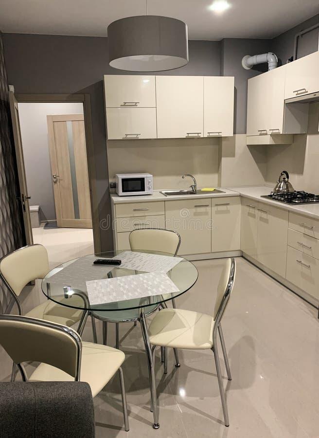 Nowożytny lekki wnętrze kuchnia z białym łomotać stołem i meble fotografia stock