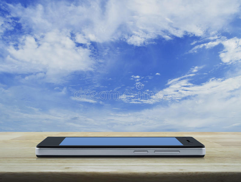 Nowożytny mądrze telefon z pustym błękitnym ekranem na drewnianym stole wewnątrz dla obraz royalty free