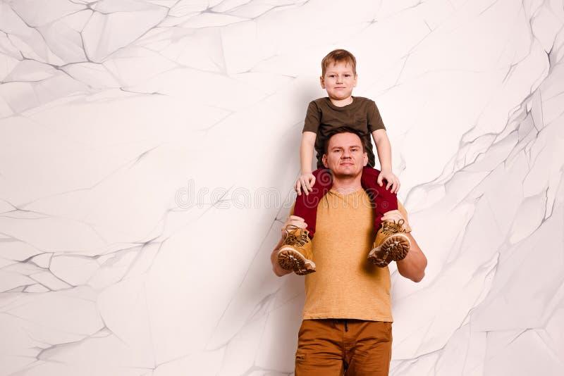Nowożytny młody człowiek trzyma ośmioletniej rozochoconej chłopiec w pomarańczowych butach wokoło jego szyi obrazy stock