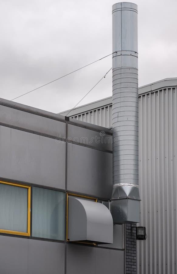 Nowożytny, metal odziany budynek biurowy, i kojarząca przemysłowa jednostka z wielkim kominem zdjęcie royalty free
