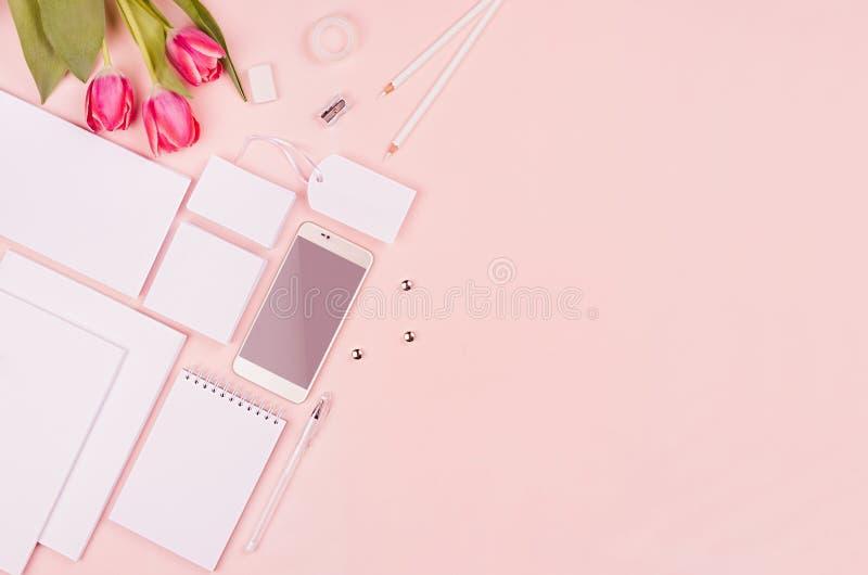 Nowożytny minimalistic wiosny workspace z białym pustym materiały, tulipany kwitnie na miękkim pastelowych menchii tle, odgórny w fotografia stock