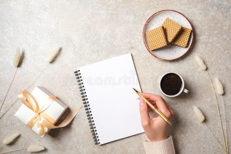 Nowożytny minimalny domowy workspace biurko z ludzką ręką pisze wiadomości tekstowej na pustego papieru notatniku, gofry, suszy k fotografia stock