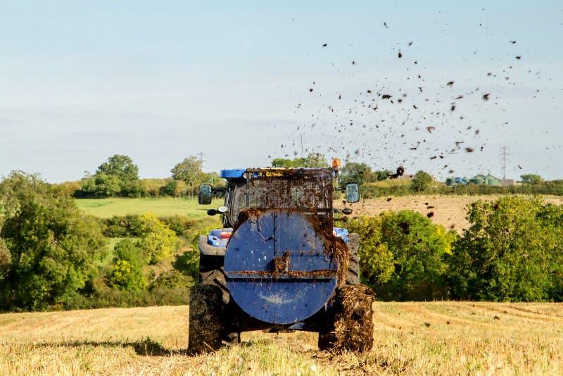Nowożytny Nowy Holandia podesłania ciągnikowy Ciągnikowy nawóz na polach zdjęcie royalty free