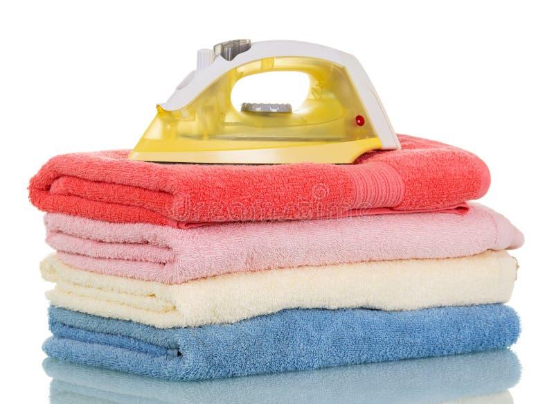 Nowożytny parowy żelazo i sterta ręczniki odizolowywający na bielu obrazy royalty free