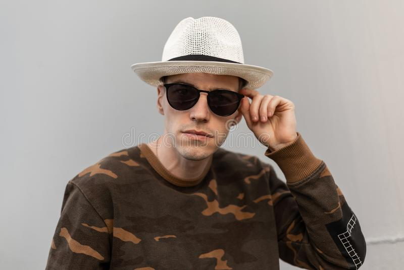 Nowożytny przystojny młody modnisia mężczyzna w rocznika słomianym kapeluszu w modnej kamuflaż koszula prostuje eleganckich okula zdjęcie stock