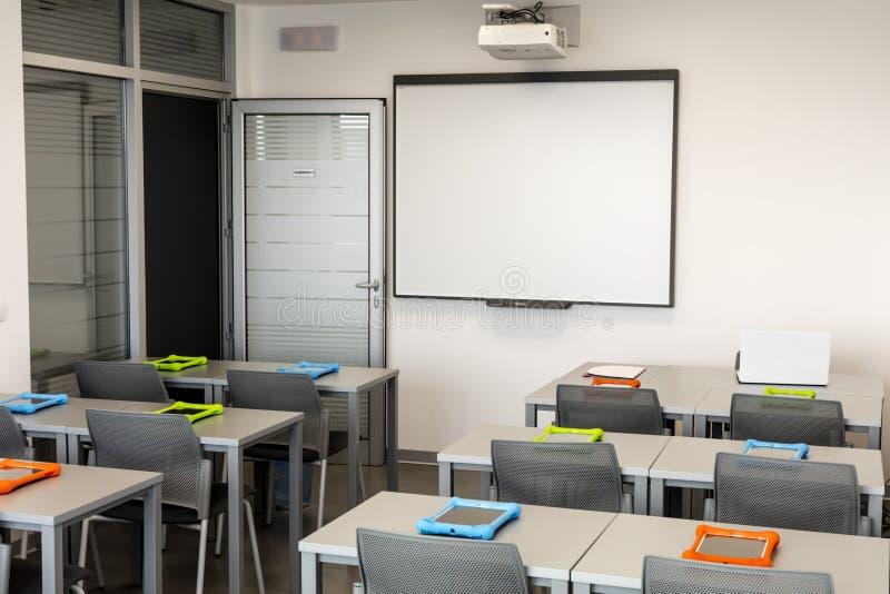 Nowożytny sala lekcyjnej wnętrze z białą deską, prac biurkami i krzesłami, fotografia stock