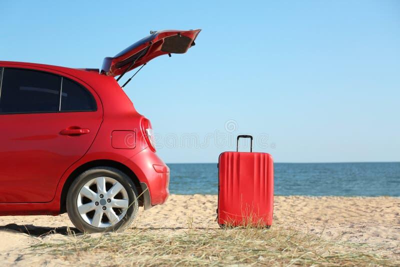 Nowożytny samochód i jaskrawa walizka na piasku blisko morza zdjęcie royalty free
