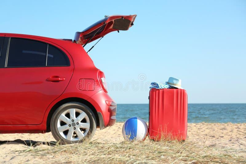 Nowożytny samochód, jaskrawa walizka i plażowi akcesoria na piasku, zdjęcie royalty free
