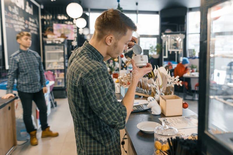 Nowożytny sklep z kawą, pracuje robić kawowemu barista, ludzie siedzi przy stołami, światło dzienne, zimy wnętrze obraz stock