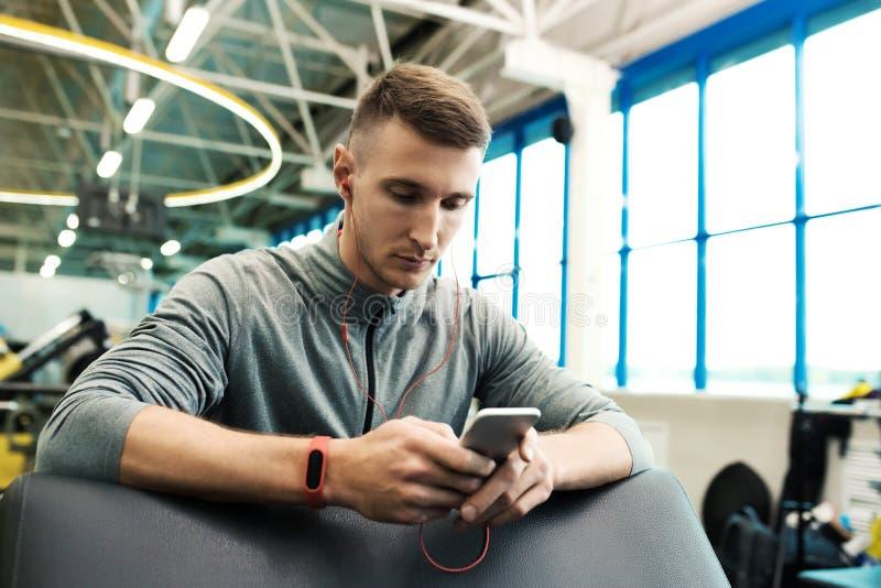 Nowożytny sportowiec używa Smartphone w Gym zdjęcia royalty free