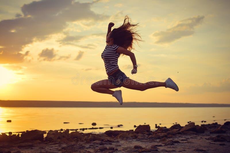 Nowożytny stylowy tancerz pozuje w w połowie powietrzu na plaży obraz royalty free