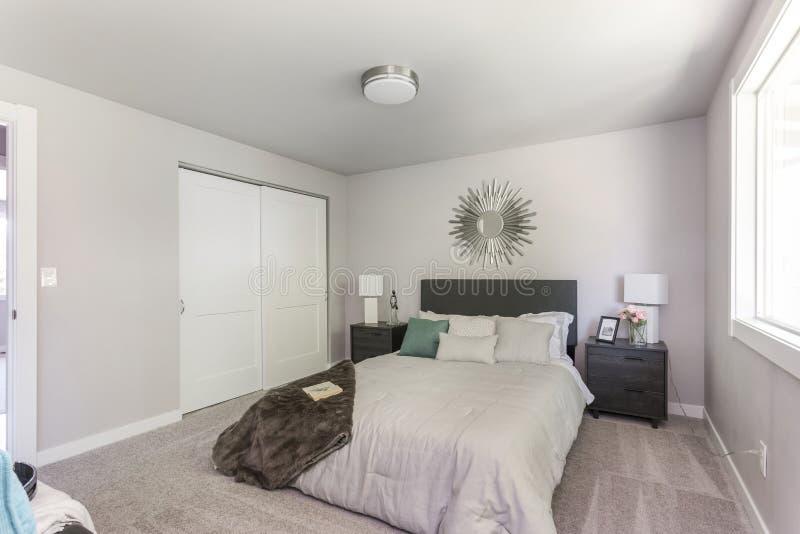 Nowożytny sypialni wnętrze z królewiątko rozmiaru łóżkiem zdjęcie stock