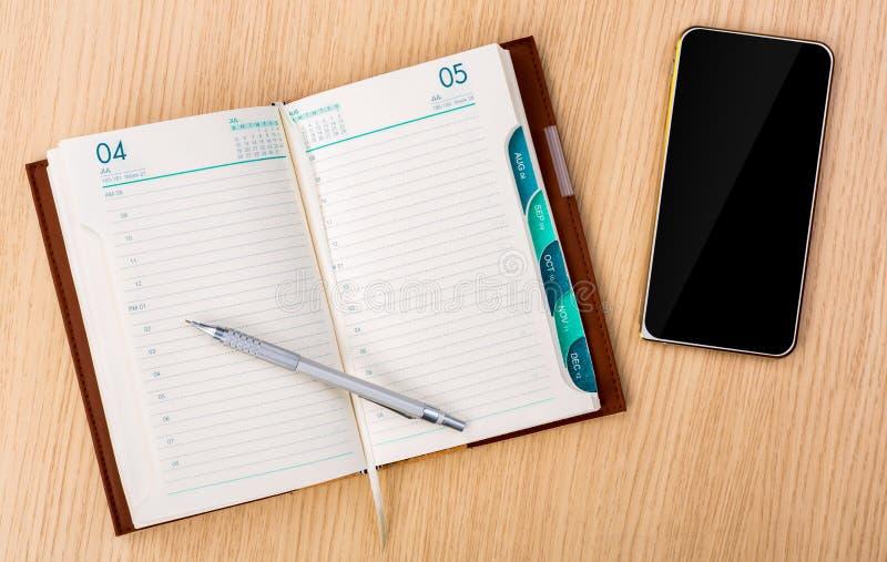 Nowożytny telefon komórkowy i roku projekt biznesowy planista rezerwujemy z obraz stock