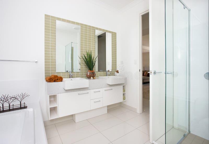 Nowożytny washroom z drzwi otwierającym i biel ścianami obrazy stock