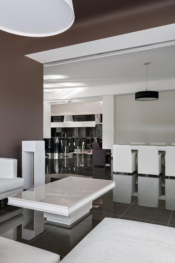 Nowożytny wnętrze z dużym stołem, krzesłami i żywym pokojem w daylig, zdjęcie royalty free