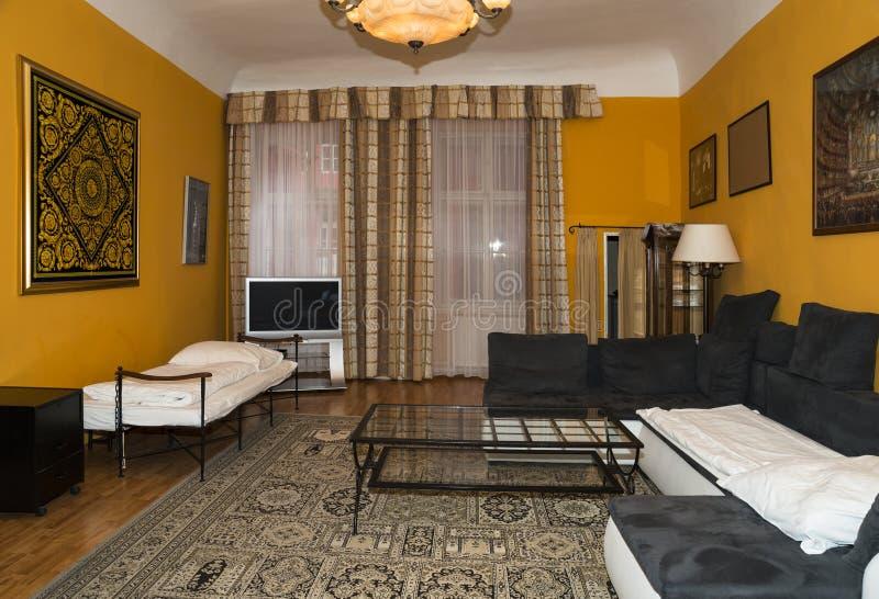 Nowoczesna konstrukcja salonu z żółtymi ścianami, dywany na podłodze i zasłonami na oknach zdjęcia stock