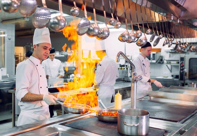 nowoczesna kuchnia Kucharzi przygotowywaj? posi?ki na kuchence w kuchni hotel lub restauracja Ogień w kuchni fotografia royalty free