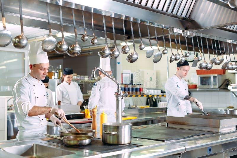 nowoczesna kuchnia Kucharzi przygotowywaj? posi?ki na kuchence w kuchni hotel lub restauracja Ogień w kuchni zdjęcie stock