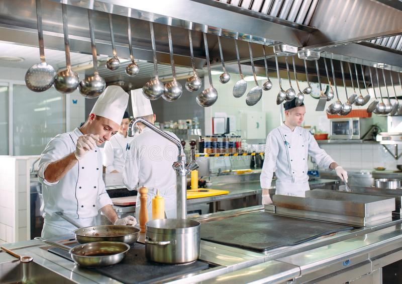 nowoczesna kuchnia Kucharzi przygotowywaj? posi?ki na kuchence w kuchni hotel lub restauracja Ogień w kuchni obrazy royalty free