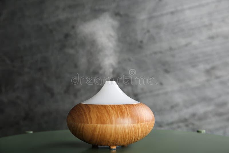 Nowoczesny dyfuzor olejowy na zielonym stole na szarym tle zdjęcia royalty free