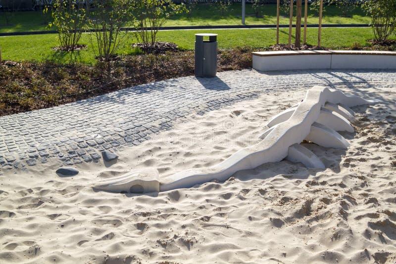 Nowoczesny plac zabaw dla dzieci z piaskownicą, w której leży szkielet dinozaura z minimalistyczną szarą puszką i drewnem obrazy royalty free
