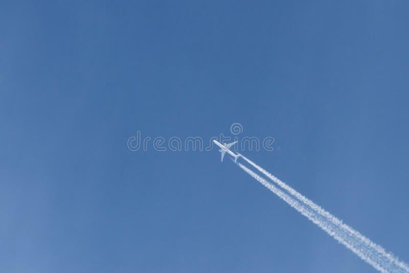 Nowoczesny samolot lecący wysoko na błękitnym niebie o słonecznej porze Prędkość i energia fotografia stock
