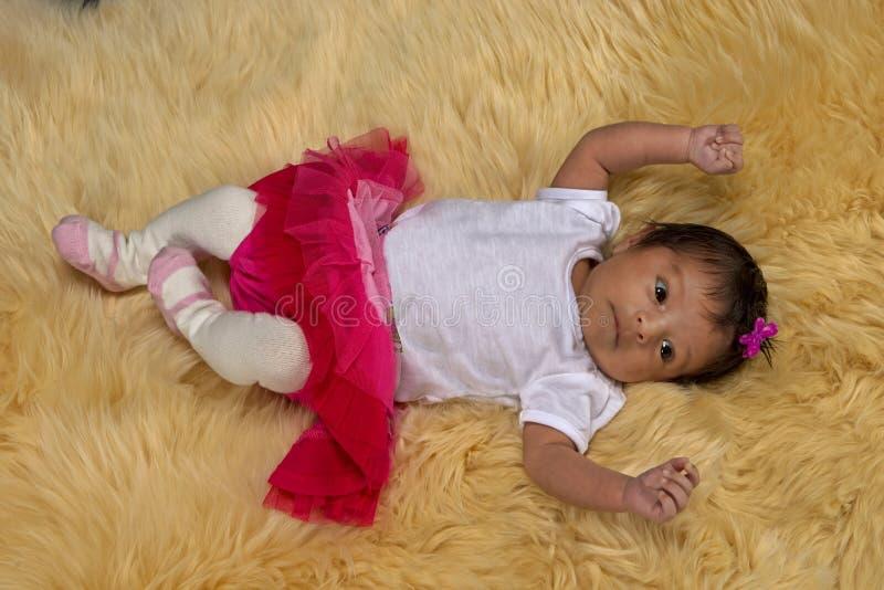 Nowonarodzona dziewczynka na pluszowym futerkowym dywaniku zdjęcia royalty free