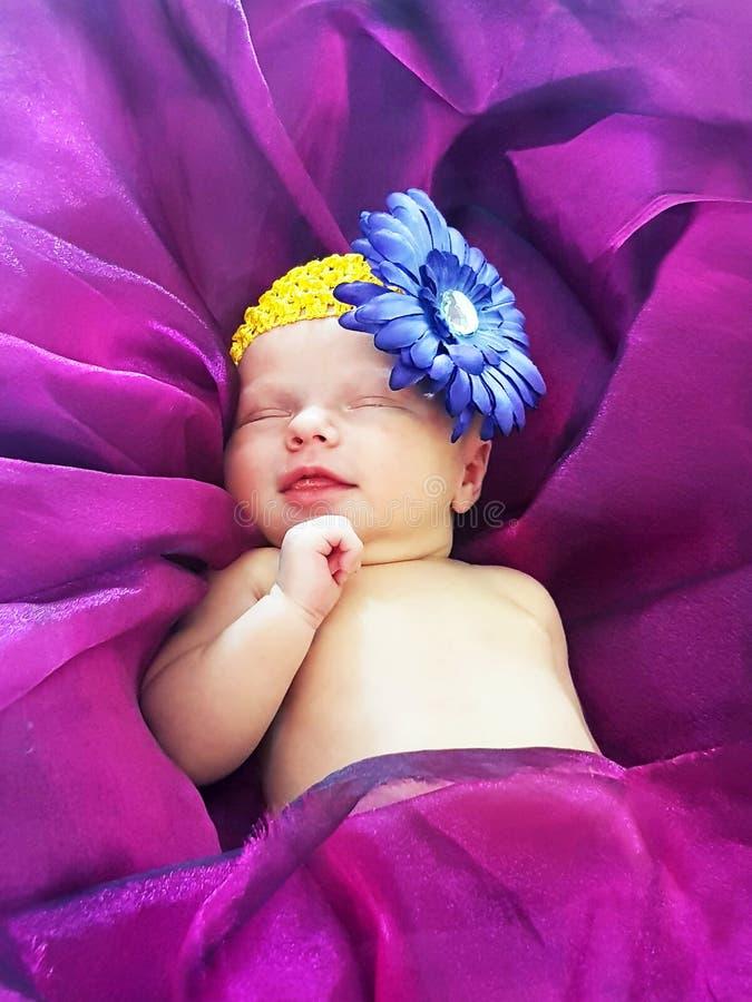 Nowonarodzonej dziewczynki uśmiechnięty dosypianie na łóżkowych ultrafioletowych purpurach fotografia royalty free