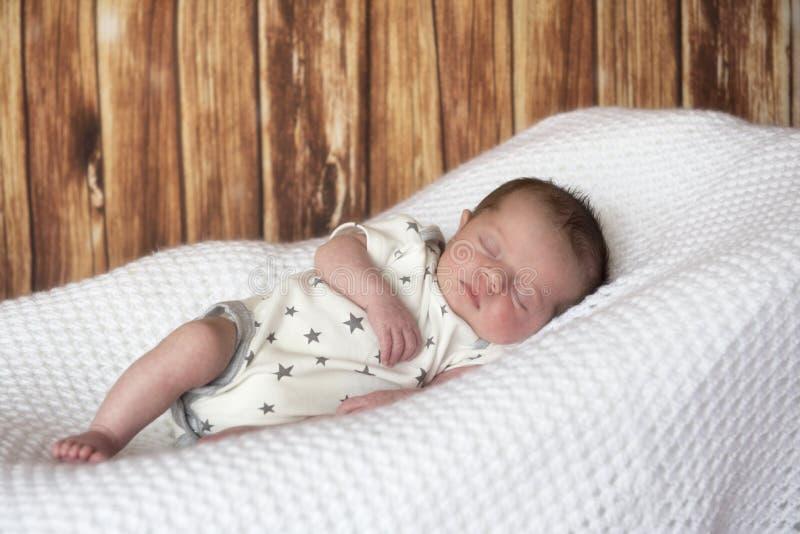 Nowonarodzony chłopiec dosypianie na białej koc obrazy royalty free