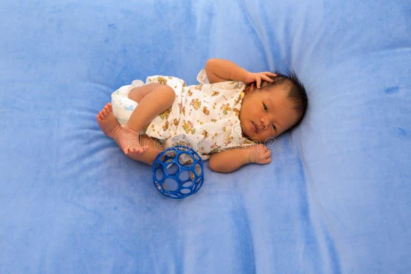 Nowonarodzony dziecka dosypianie na błękitnym futerkowym tkaniny łóżku obraz royalty free