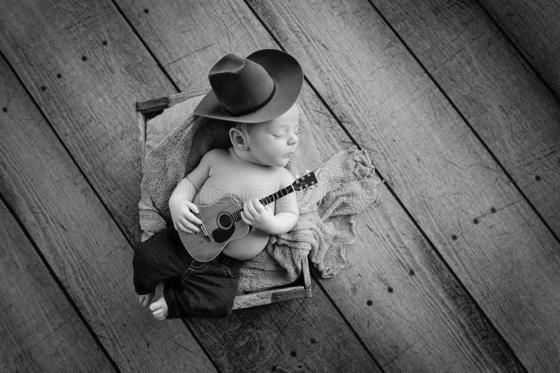 Nowonarodzony dziecko kowboj Bawić się Malutką gitarę zdjęcie royalty free