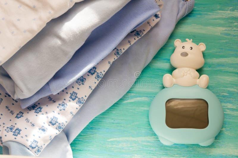 Nowonarodzony dziecko odzieżowy i błękitny na drewnianym tło children pokoju palowi akcesoria obrazy stock