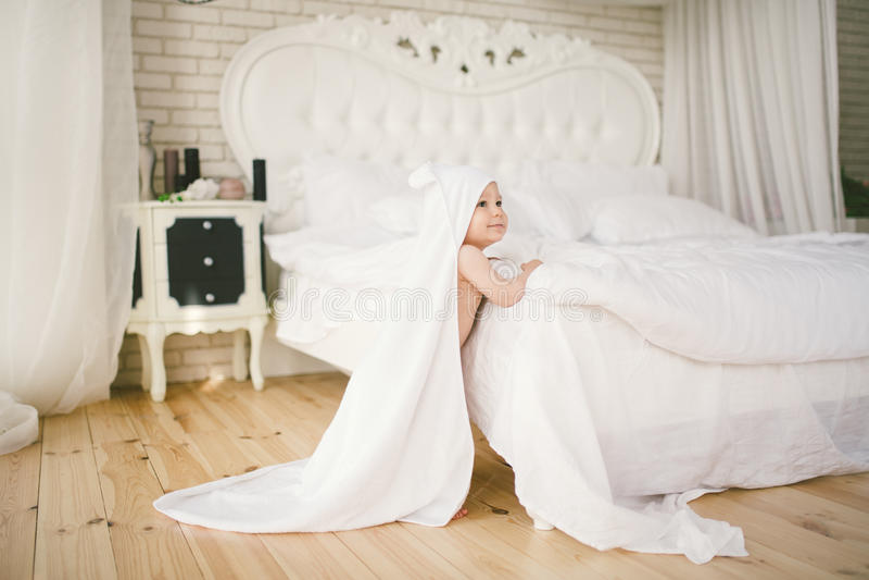 Nowonarodzony dziecko pięć miesięcy stary dziecko w sypialni obok wielkiego białego łóżka na drewnianej podłoga zawijającej w bia zdjęcie royalty free