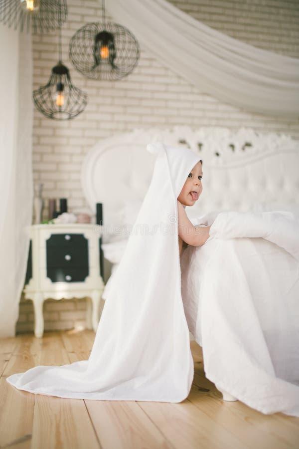 Nowonarodzony dziecko pięć miesięcy stary dziecko w sypialni obok wielkiego białego łóżka na drewnianej podłoga zawijającej w bia fotografia stock