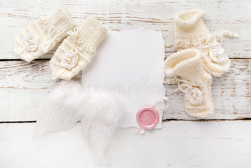 Nowonarodzony lub ochrzczenie kartka z pozdrowieniami Puste miejsce z dziewczynka butami, rękawiczkami i anioła wingson białym dr obrazy stock