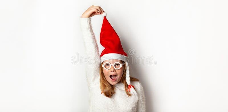 Noworoczne zamieszanie i zamieszanie, dziewczyna w czapce Świętego Mikołaja trzyma czapkę ręką, odizolowana na białym tle zdjęcie stock